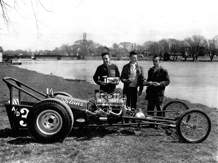 Boys standing by a Drag Racer with Chippawa Creek in the background (image/jpeg)