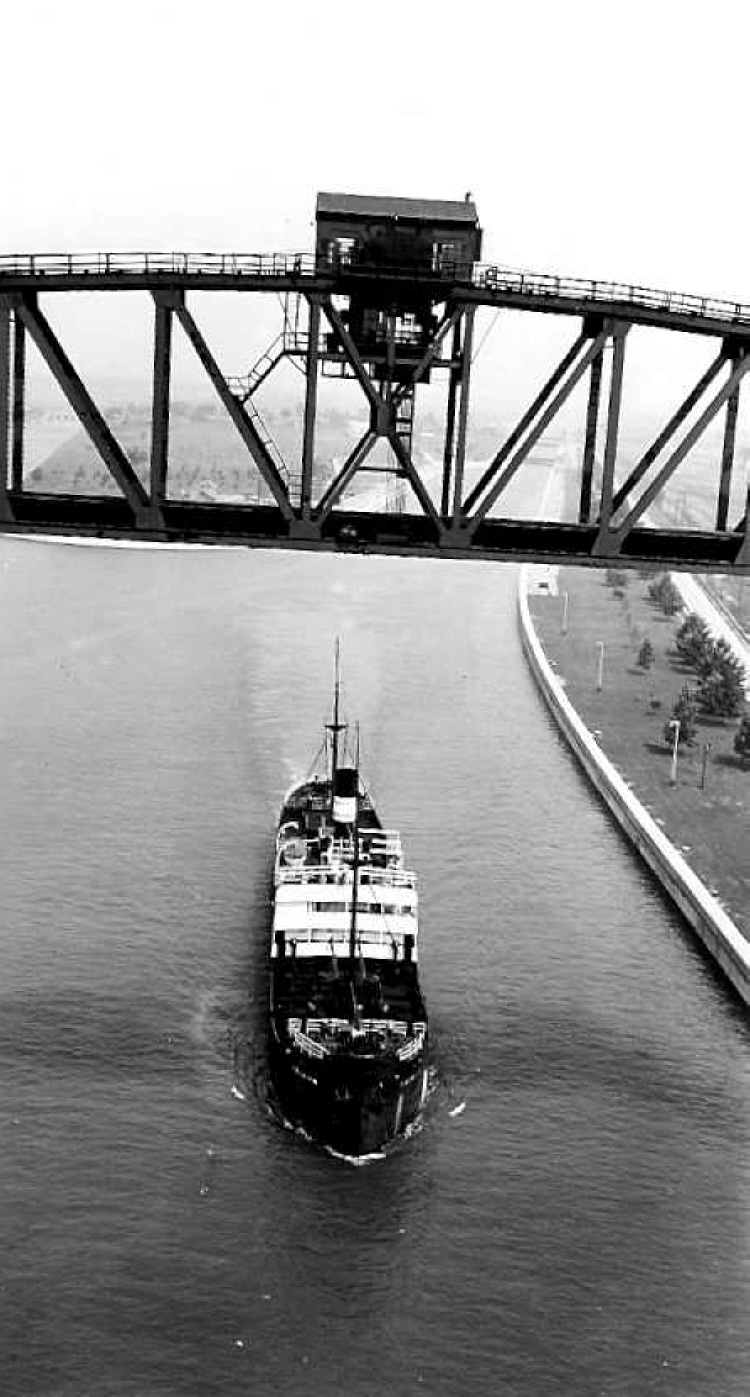 Aerial of a Ship in the Welland Canal Passing Under a Lift Bridge (image/jpeg)