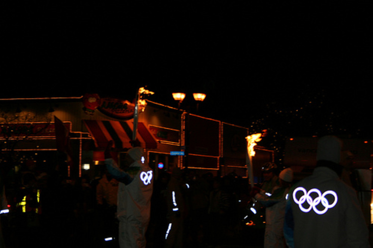 2010 Olympic Torch Relay in Niagara Falls - Torch Being Carried Down Queen Street & Passed on to Next Torchbearer 5 (image/jpeg)