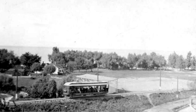 An Electric Streetcar travelling through Lakeside Park in Port Dalhousie, Lake Ontario in the background (image/jpeg)