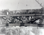 (Thumbnail) Construction workers gather on the newly completed Lower Steel Arch Bridge at Niagara Falls, train in background (image/jpeg)